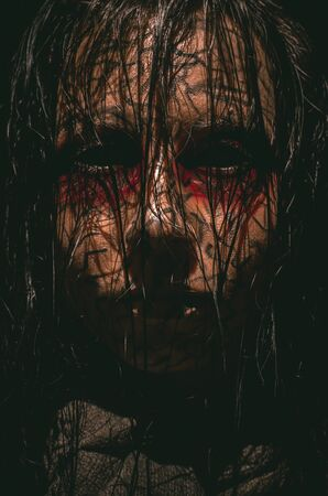 Spooky infernal girl with black eyes and cracked skin close-up portrait on dark background