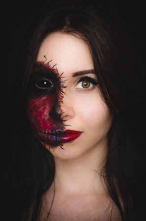 Portrait effrayant d'une femme aux yeux noirs et une marque maudite sur son visage sur fond sombre. Nature démoniaque dans un corps innocent Banque d'images