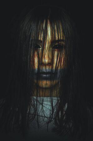 Sorcière effrayante aux yeux noirs sur fond sombre. Affiche pour un film d'horreur