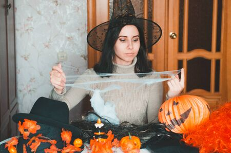 Young woman in witch hat prepares for halloween and keeps fake spiderweb among holiday decorations and elements for costumes
