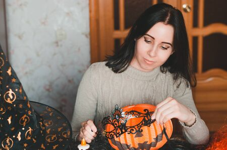 Young woman prepares for halloween and keeps masquerade mask among holiday decorations and witch hat