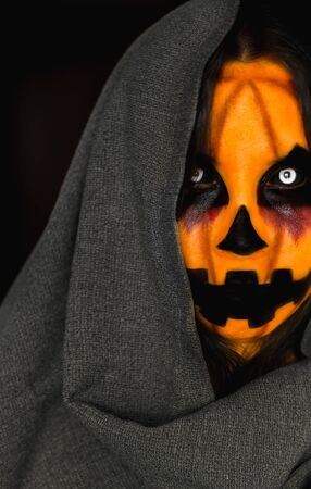 Creepy pumpkin face of a scarecrow in a hood. Close-up halloween costume portrait of a spooky monster with white eyes