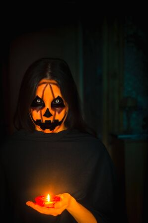 Frightening pumpkin face character hold a candle. A portrait of a halloween creature in the darkness with copy space