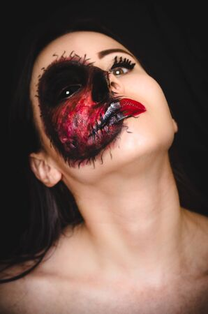 Creepy portrait of a woman with black eye and a horrible cursed mark on her face on dark background. Demonic nature in an innocent body concept