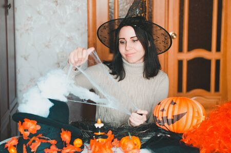 Young caucasian woman in witch hat prepares for halloween and keeps fake spiderweb with smile among holiday decorations and elements for costumes