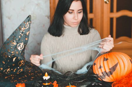 Young woman getting ready for halloween and keeps fake spiderweb among holiday decorations and elements for costumes. Portrait indoors Reklamní fotografie
