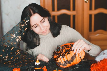 Young smiling woman prepares for halloween and keeps a masquerade mask among holiday decorations and witch hat Banco de Imagens