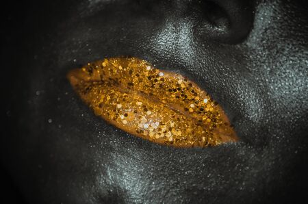 Gold lips with glitter close-up female face on dark background. Trendy colours concept
