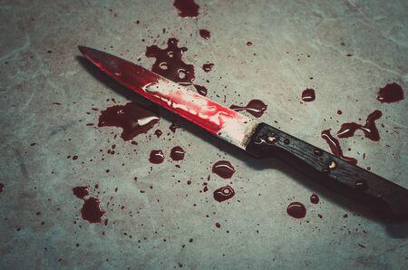 Blutiges Messer liegt auf hellem Hintergrund mit dunkelroten Tropfen. Konzept eines häuslichen Mordes und Horrorfilme