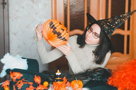 Young caucasian woman with glasses in witch hat prepares for halloween and keeps a pumpkin lantern among holiday decorations and elements for costumes