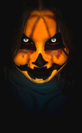 Scary pumpkin face of a halloween creature with gloomy look and creepy smile on dark background. Close-up vertical portrait of a monster with copy space