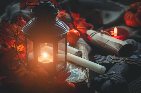 Close-up glowing lantern and different medieval or a fairy tale objects such as candles, a rolled letter, a sword and a book on textile background. Cozy autumn background