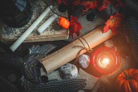 Different medieval or a fairy tale attributes such as candles, a rolled letter, a sword and a book on textile background. Historic autumn backdrop