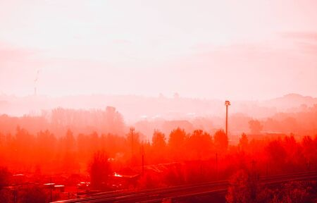 Red autumn forest and mist in a small town in the morning. Seasonal vivid horizontal background with copy space Reklamní fotografie