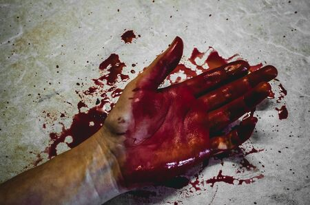 Main d'une personne tuée dans une flaque sanglante. Concept d'une victime de meurtre Banque d'images