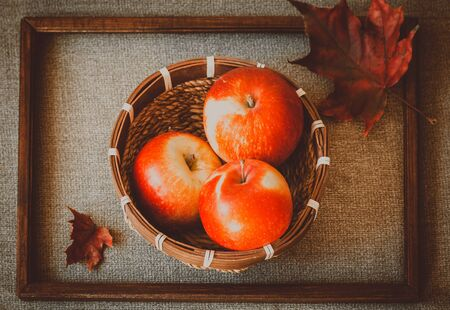 Three red apples in a basket and two autumnal leaves with wooden frame