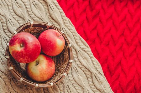 Three apples in the basket on knitted background. Concept of cozy autumn mood and harvest