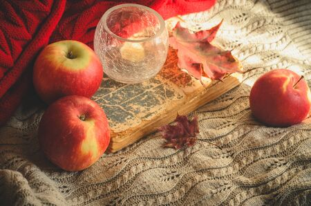 Three apples, candle, red leaves and old book on knitted background. Concept of cozy autumn mood or reading Reklamní fotografie