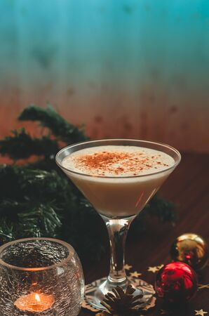 Traditional christmas eggnog with fir branch, burning candle, two balls on wooden background. Copy space Reklamní fotografie