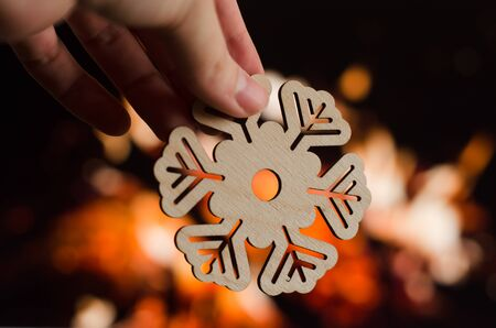Close-up wooden snowflake christmas decoration on fireplace background. Holiday cozy scene