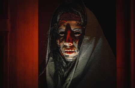 Creepy halloween witch with black eyes, scars on her face in a hood stands near opened doors in the night. Portrait of a scary creature from another world