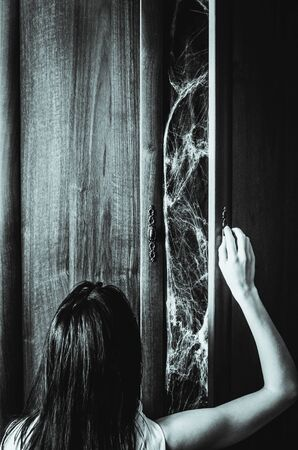 Young woman opens a door of an old wardrobe with spiderweb something creepy inside. Black and white vertical poster for a horror movie with copy space. Fear of the dark concept Reklamní fotografie