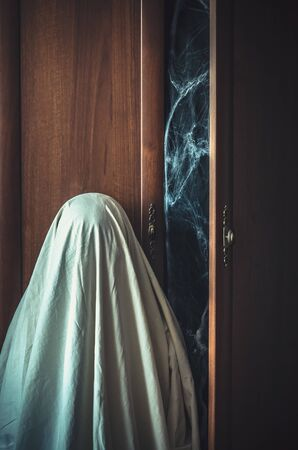 A ghost stands near an old creepy wardrobe. Halloween creature and vertical poster for a horror film with copy space