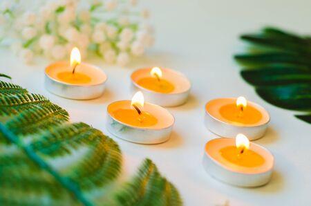 Fünf brennende Kerzen mit kleinem Blumenstrauß und grünen Blättern auf weißer Hintergrundnahaufnahme. Entspannungs- und Aromatherapiekonzept