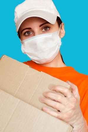 Delivery girl wears medical face mask and gloves and holds two boxes close-up portrait. Concept of safe services during covid-19 outbreak. Courier on blue background