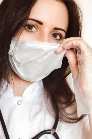 Young female doctor wears virus protection face medical mask and gloves. Close-up portrait