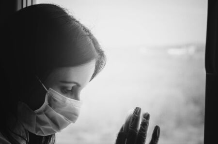 Young caucasian woman with dark hair in medical virus protection face mask and glove near the window. Self-isolation quarantine concept against covid-19 outbreak Imagens - 143771031