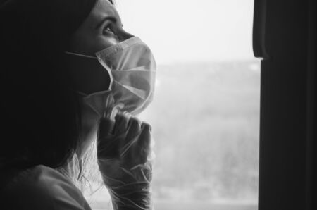 Tired doctor in a medical face mask and protection glove near the window. Concept of fighting against diseases including covid-19 outbreak