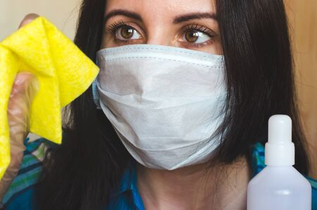Close-up portrait of a woman in a medical virus protection mask with a rag and antibacterial agent. Concept of disinfection and hygiene during covid-19 outbreak