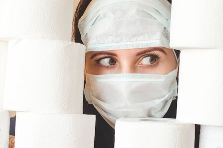 Scared person in two medical virus protection face masks looks through stacks of toilet paper. Covid-19 quarantine panic and deficit concept Imagens - 144991890