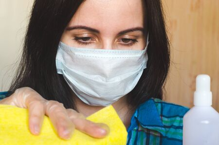 Woman in a medical virus protection mask with a rag and antibacterial agent cleans her house. Close-up portrait. Concept of disinfection and hygiene during covid-19 outbreak Stock fotó