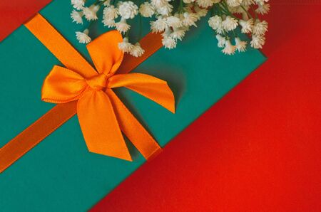 Gift with ribbon and white flowers lie on red background top view copy space minimalistic greeting card