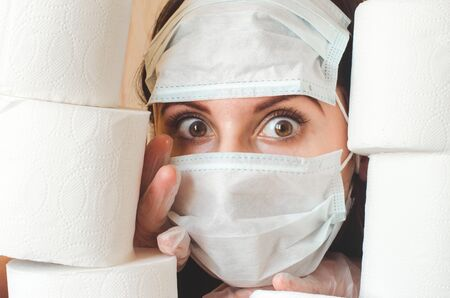 Young woman with big scared eyes in two medical virus protection face masks looks through stacks of toilet paper. Covid-19 lockdown panic and deficit concept