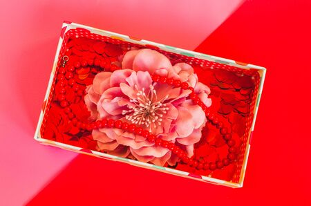 Small gift box with flower, little hearts and beads on duotone pink red background top view Imagens - 146608399
