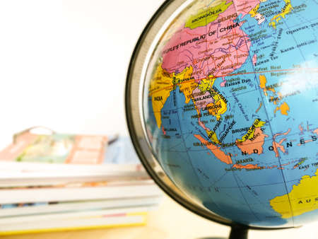 Countries and continents close up with the color map on a globe with books in the background. Education and travel concept. Editorial