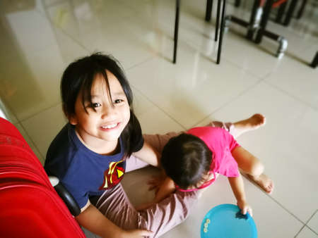 Two little asian children, sisters and siblings playing at home.