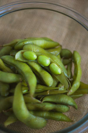 Close up portrait of Japanese food edamame nibbles, boiled green soybeans in a bowl on a burlap background.