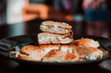 """Nahaufnahme des bekannten malaysischen Essens """"Roti John"""" auf dunklem Hintergrund. John-Brot oder """"Roti John"""" aus Eiern, Hackfleisch und Brot, serviert mit geschmolzenem Käse. Beliebt während des Ramadan. Standard-Bild"""