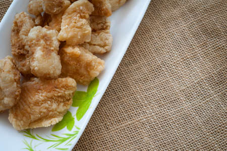 Malaysian style battered and deep fried dory fish cubes. Served in a long plate on a brown background.