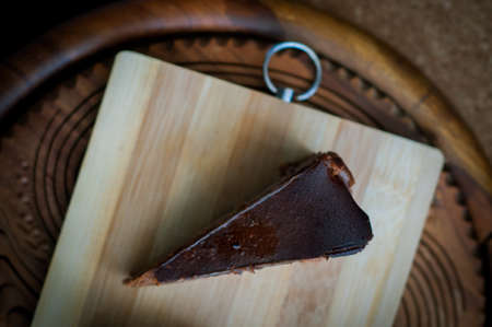 Burnt chocolate cheesecake on brown wooden background. selective