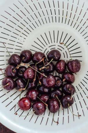 Fresh cherry on white basket. fresh ripe cherry being washed before eaten.