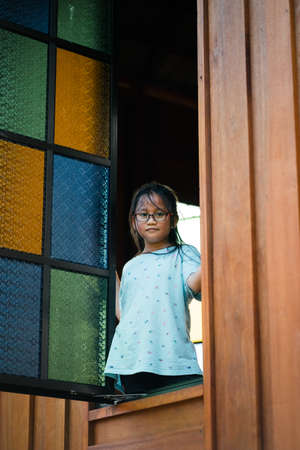 Young girl next to the Multicolored stained glass window with rectangular pattern in blue, yellow and green attached to a traditonal Malay house.