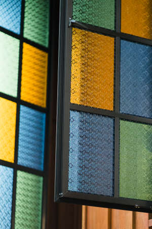 Multicolored stained glass window with rectangular pattern in blue, yellow and green attached to a traditonal Malay house.