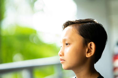Portrait of a teenage Asian boy with emotion. Good hair cut and personality. 免版税图像