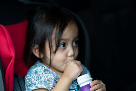 Adorable asian toddler girl in safety car seat. Drinks from the bottle.