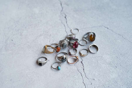 Vintage collection of man's old rings on the concrete background. Stock Photo
